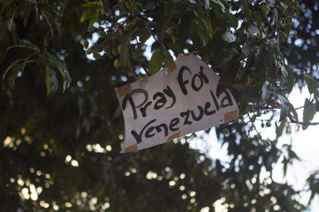 Un cartel en un árbol pide por Venezuela.