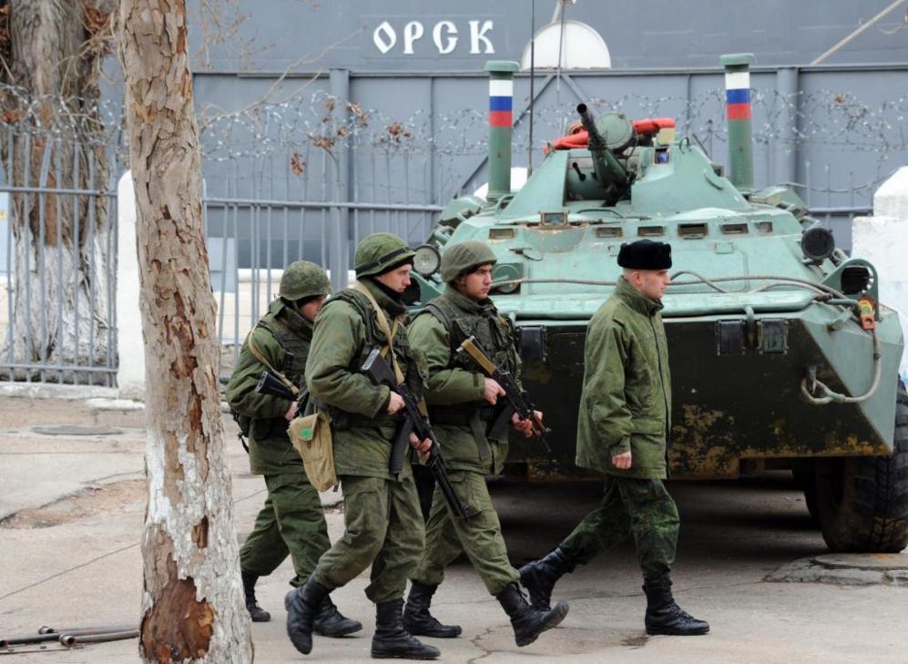 Soldados de infantería rusa caminan delante de un blindado en la...