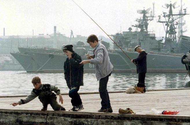 Varios niños jugando con un buque de guerra ruso atracado en el...