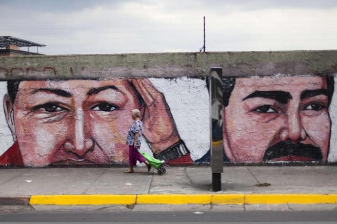 Dos pintadas con imágenes del expresidente Hugo Chávez y su sucesor,...