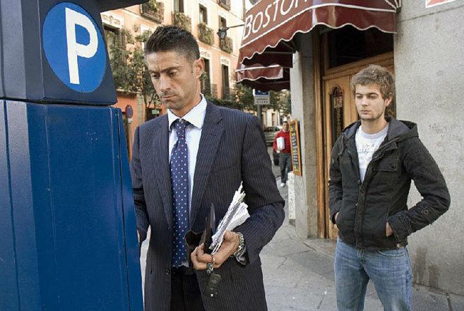 Dos personas sacan el ticket del parquímetro en el centro de Madrid.