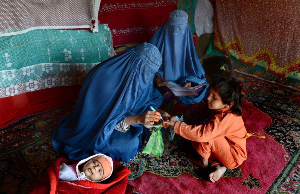 Unas trabajadoras sanitarias afganas vestidas con burkas marcan el...