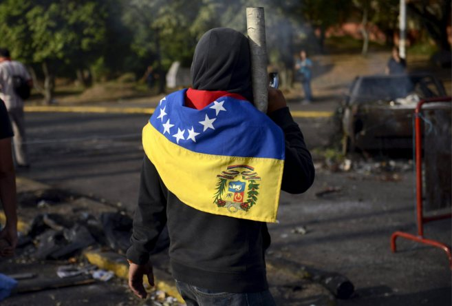Una manifestante venezolano custodia una barricada en la localidad de...