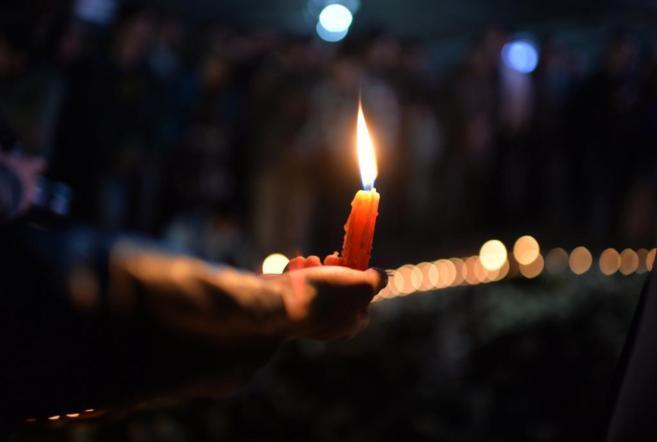 Una vela encendida durante una vigilia por la masacre de Kunming.