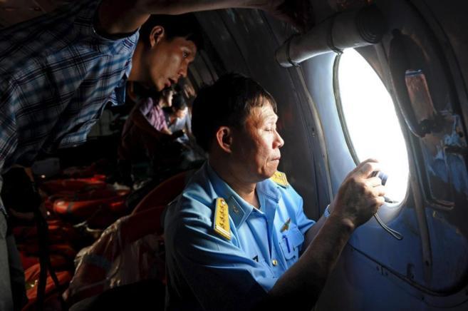 Un oficial y un periodista miran por la ventanilla de un avión...