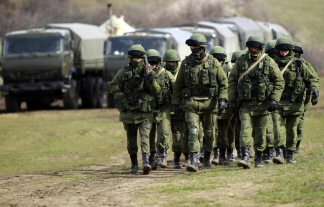 Hombres armados, previsiblemente soldados rusos, caminan hacia una...