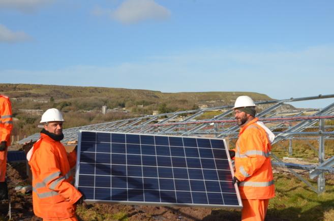 Dos de los trabajadores instalan paneles fotovoltaicos en Cornualles...