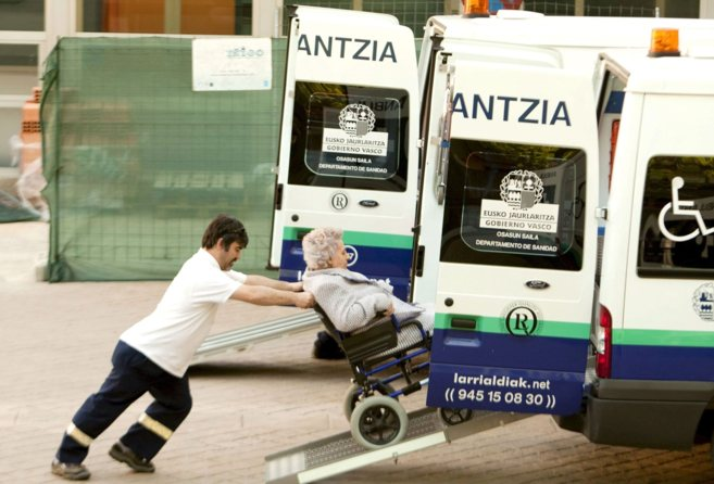Un trabajador de ambulancias sube a una anciana al vehículo en...