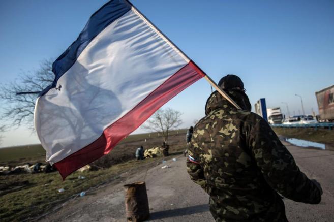 Un soldado prorruso sostiene una bandera rusa a la entrada de Crimea.