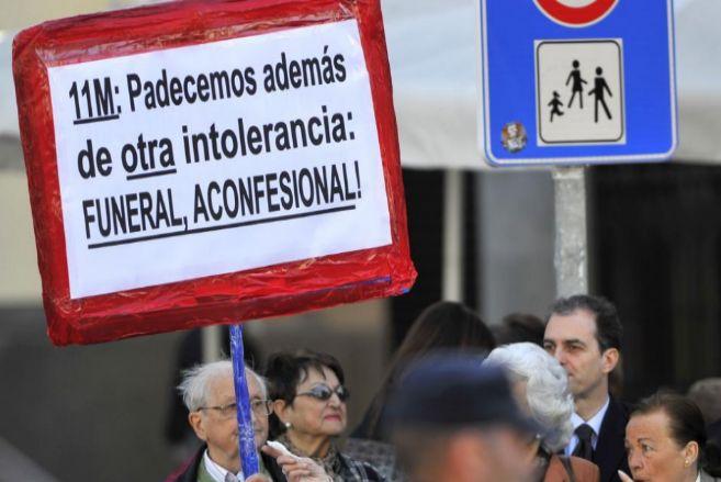 Un hombre protesta por el funeral católico en La Almudena.