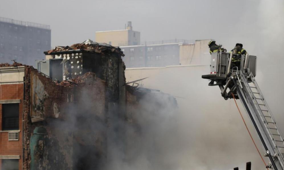 Bomberos tratan de extinguir el fuego tras derrumbarse por una...