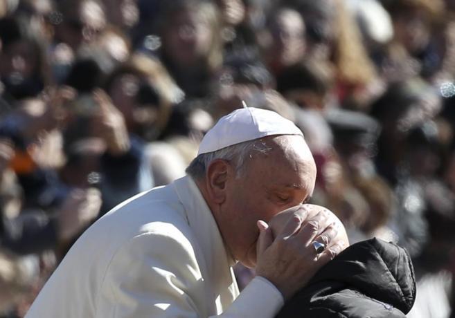 El Papa Francisco besa a un niño en la plaza de San Pedro