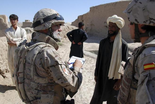 Un militar español habla con un afgano con ayuda de un traductor en...