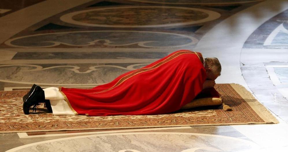 El Papa reza tendido en el suelo, durante la celebración del Viernes Santo en la Basílica de San Pedro en el Vaticano, al comienzo de la Pasión de Cristo.