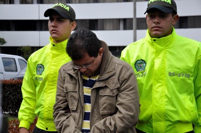 El detenido, custodiado por dos agentes colombianos.
