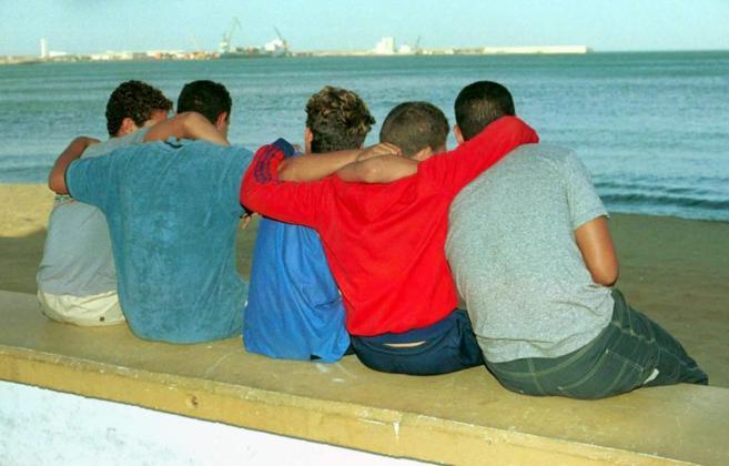 Varios niños sentados en un muro frente a una playa.