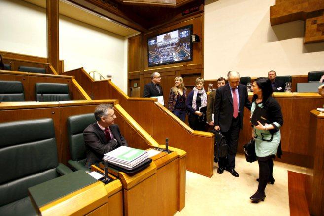 Urkullu en su escaño mientras entran al pleno los parlamentarios.