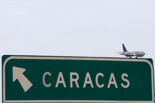 Un avión sobrevuela un cartel indicando la dirección de Caracas en...