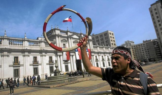 Un mapuche se manifiesta frente al Palacio de la Moneda.