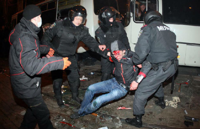 Agentes antidisturbios sujetan a un manifestante herido en la cabeza...