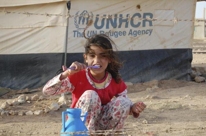 Una niña se lava los dientes ante una tienda de lona, en el campo de...