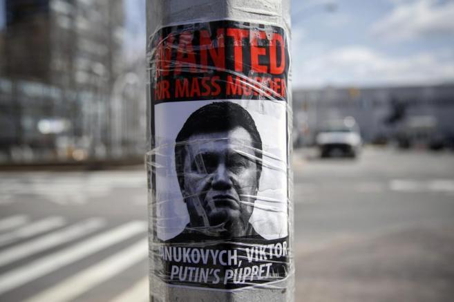 Un cartel del depuesto presidente Yanukovich con el rótulo 'Se...