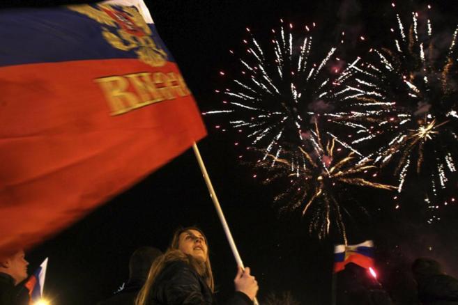 Una mujer sostiene una bandera rusa en la celebración de los...