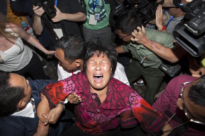 Una mujer, familiar de un pasajero del vuelo MH370, rompe a llorar en...