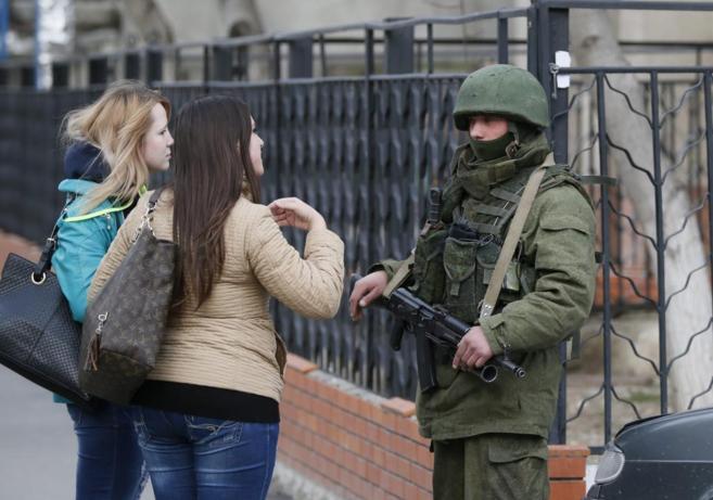 Un miembro de un destacamento ruso habla con civiles en una calle de...