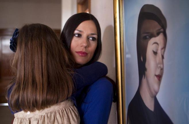 Una mujer sostiene a su hijas en brazos mientras mira el retrato de...