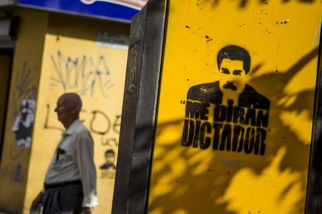 Un hombre pasa ante un grafiti contra Maduro.