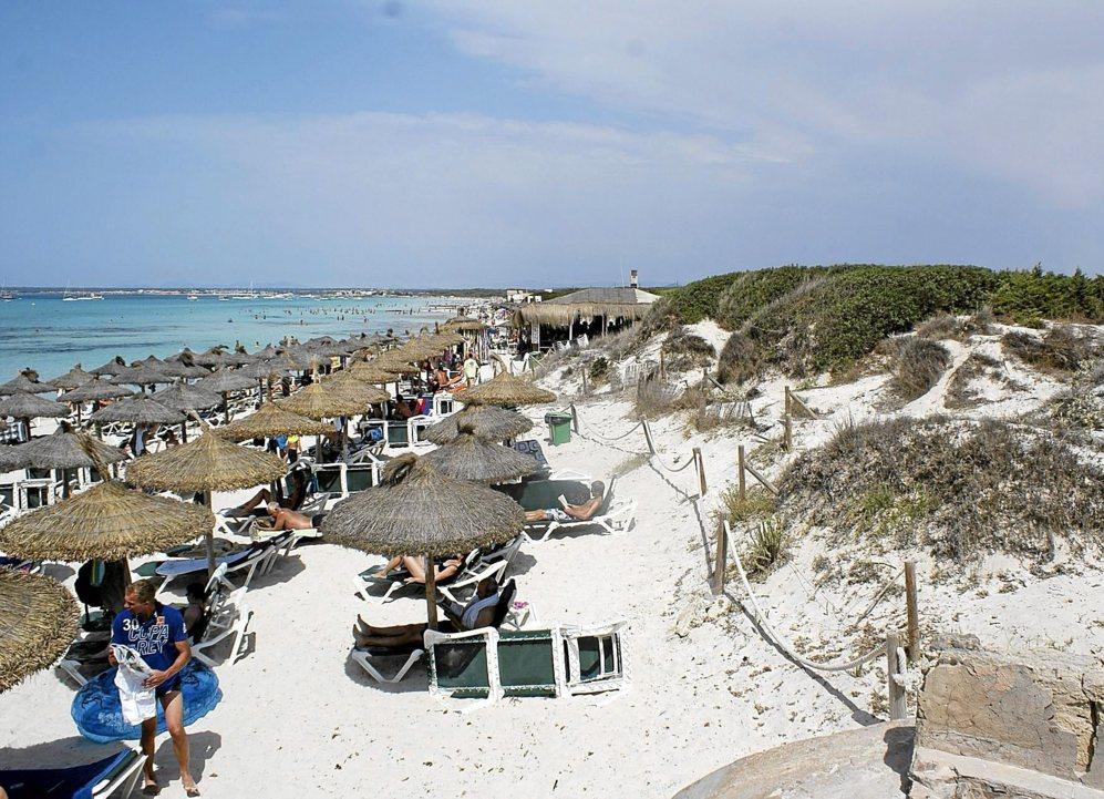 La playa de Ses Covetes, con las hamacas y las sombrillas en primer...