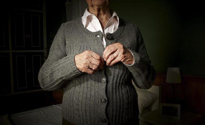 Una mujer con Alzheimer se abrocha la chaqueta.