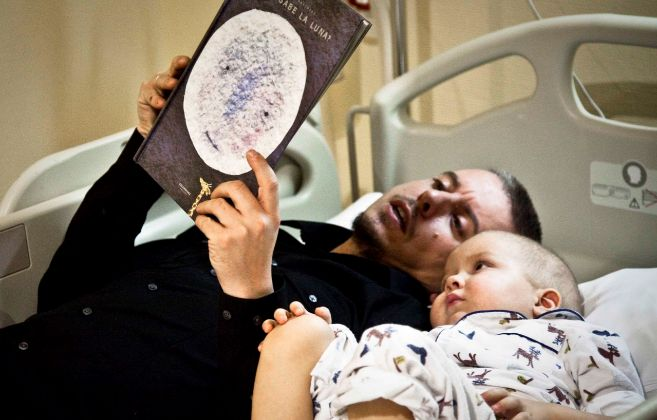 Un padre lee un cuento a su hijo tumbados en la cama de un hospital