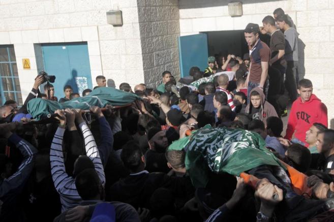 Una multitud portan los cuerpos de tres de los muertos en el campo de...