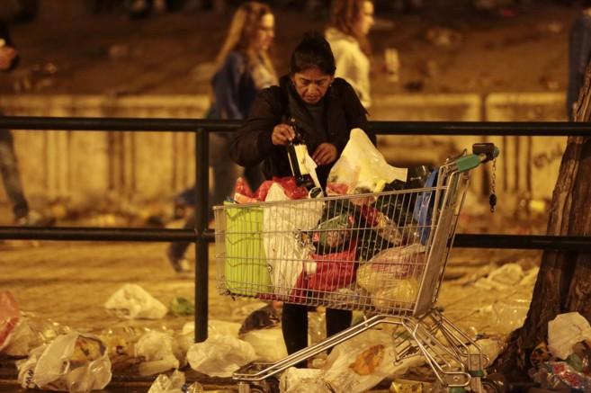 Una mujer llena un carrito con botellas, en la madrugada del sábado...