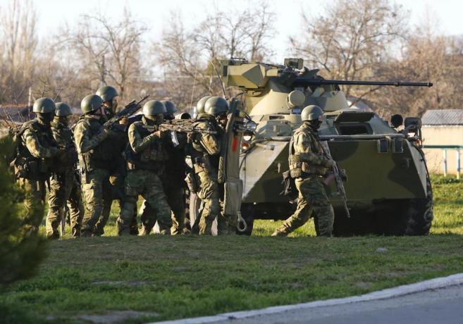 Hombres armados, probablemente rusos, junto a un vehículo blindado, a...