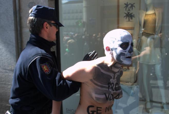 Una activista de Femen es retenida por un agente durante la marcha de...