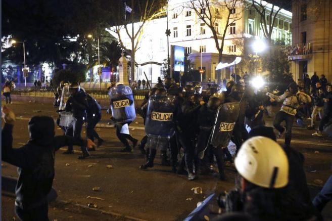 Manifestantes pegan y tiran piedras a un grupo de policías que...
