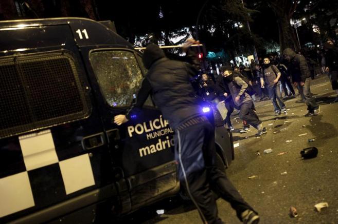 Un manifestante ataca un furgón policial.