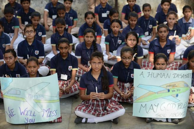 Escolares indios muestran carteles con dibujos suyos del avión...