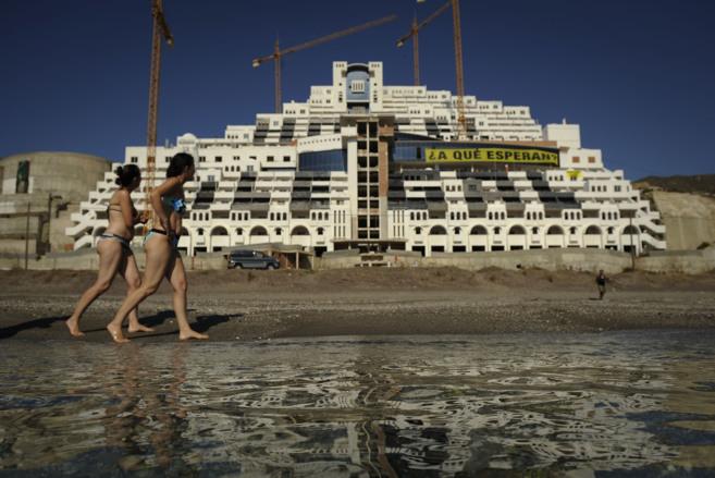 Dos bañistas pasan junto al hotel de El Algarrobico durante las...