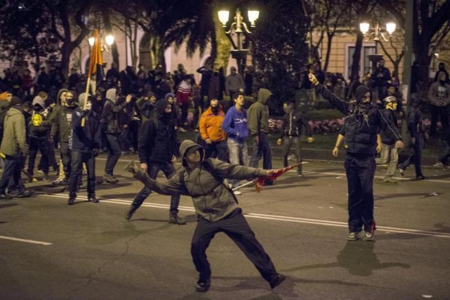 Un joven tira una piedra al término de las Marchas de la Dignidad.