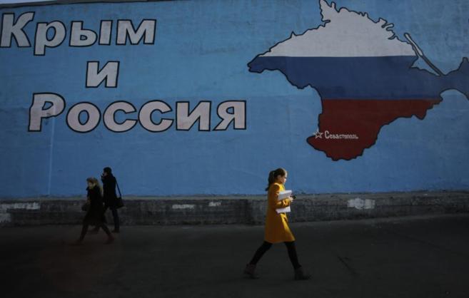Varias personas pasan delante de un cartel de Crimea pintado con los...