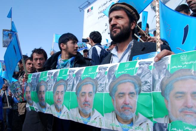 Jóvenes afganos con carteles electorales de uno de los candidatos...
