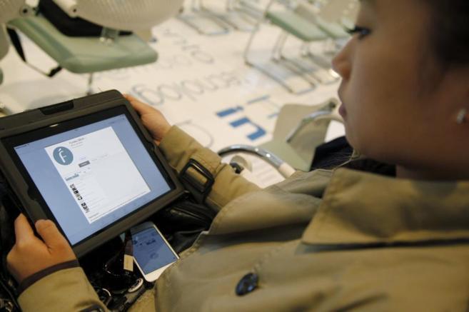 Una periodista prueba la aplicación en su tableta, durante la...