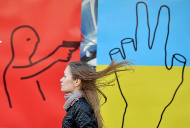 Una joven pasa ante un mural que condena la violencia en la capital de...