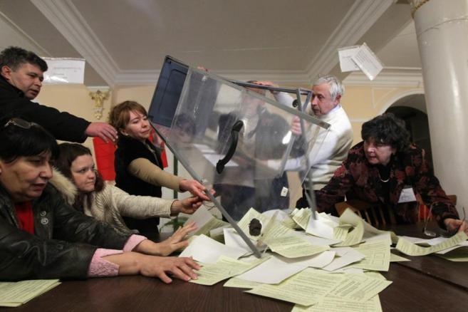 Miembros de una comisión electoral cuentan papeletas en el...