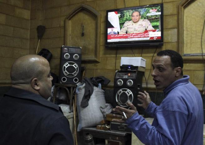 Gente escucha a  Abdelfatah al Sisi, jefe de las Fuerzas Armadas de...