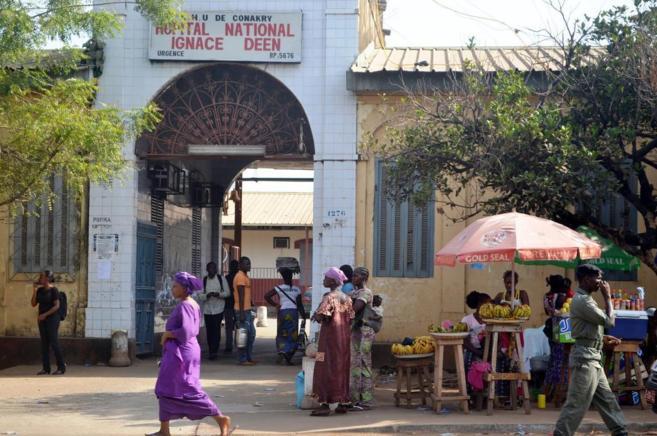 Gente caminando frente a un hopital en la ciudad de Conakry.